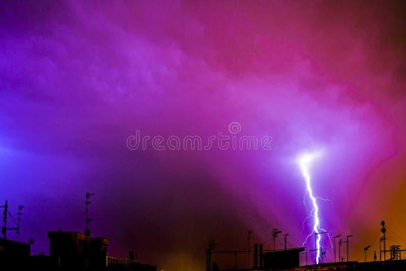 Colpo di fulmine nella città alla tempesta di notte fotografia stock libera da diritti
