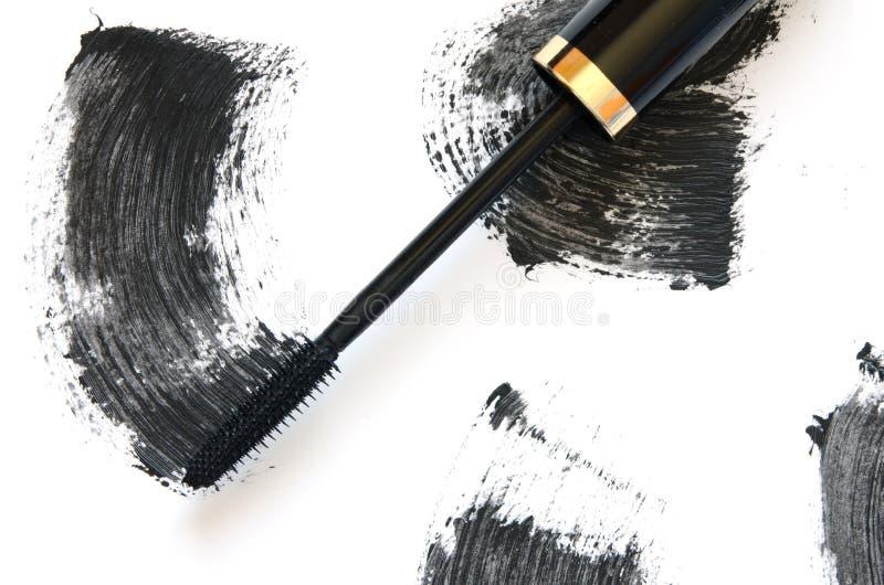 Colpo di mascara nera con il primo piano della spazzola dell'applicatore, isolato su fondo bianco fotografia stock libera da diritti