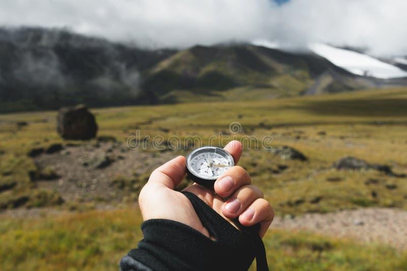 Colpo di punto di vista Una vista in prima persona di una mano del ` s dell'uomo tiene una bussola contro lo sfondo di un paesagg fotografia stock libera da diritti