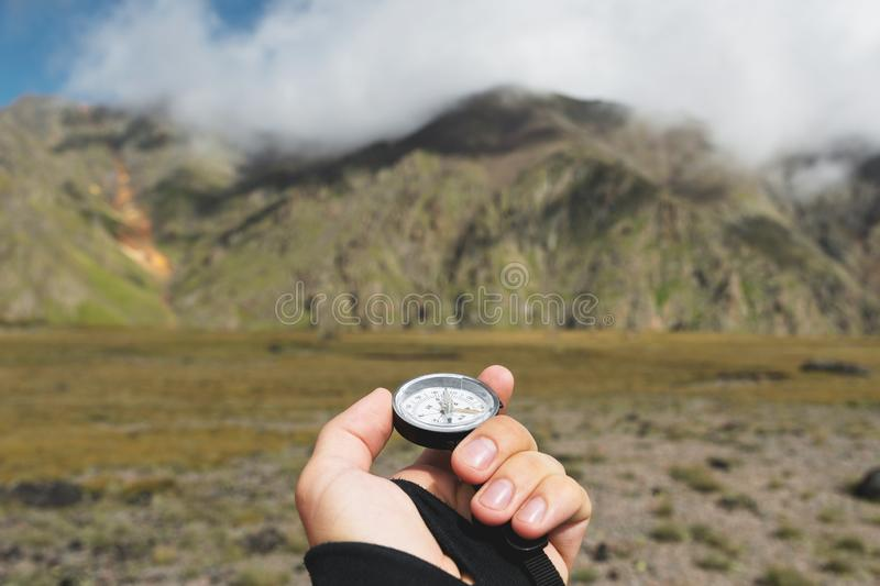 Colpo di punto di vista Una vista in prima persona di una mano del ` s dell'uomo tiene una bussola contro lo sfondo di un paesagg immagini stock