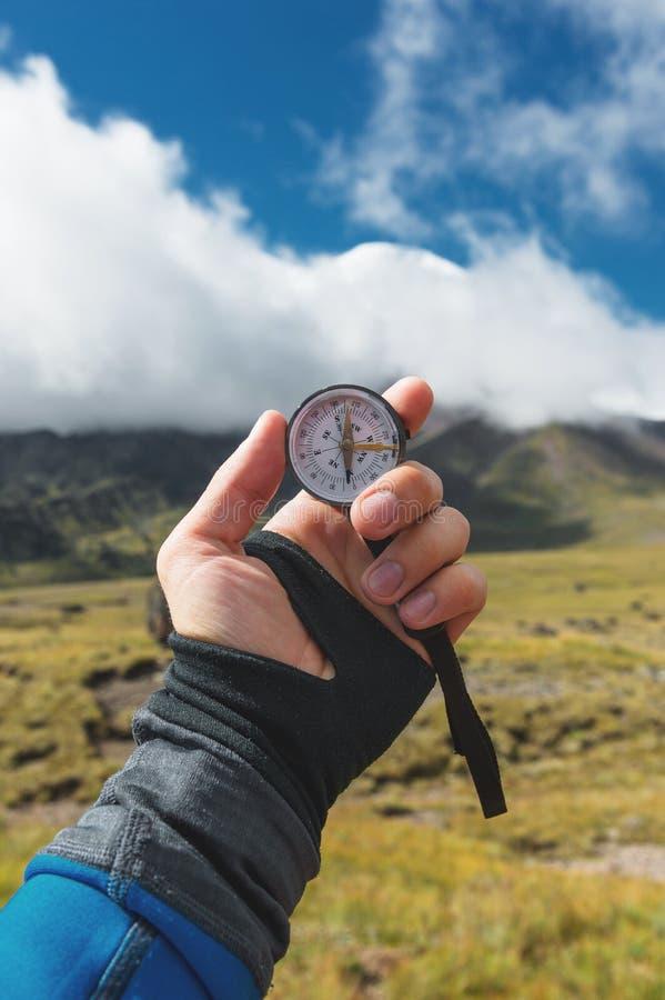 Colpo di punto di vista Una vista in prima persona di una mano del ` s dell'uomo tiene una bussola contro lo sfondo di un paesagg fotografie stock libere da diritti