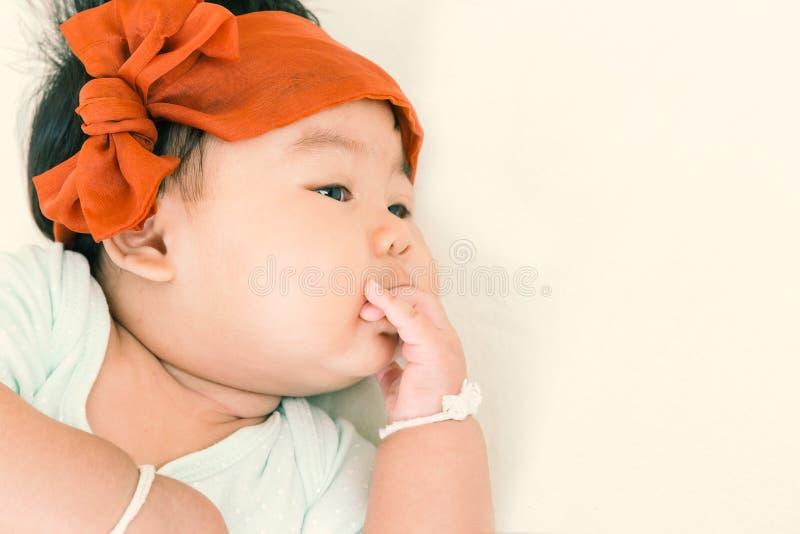 Colpo di succhiamento del bambino asiatico adorabile sul letto fotografie stock