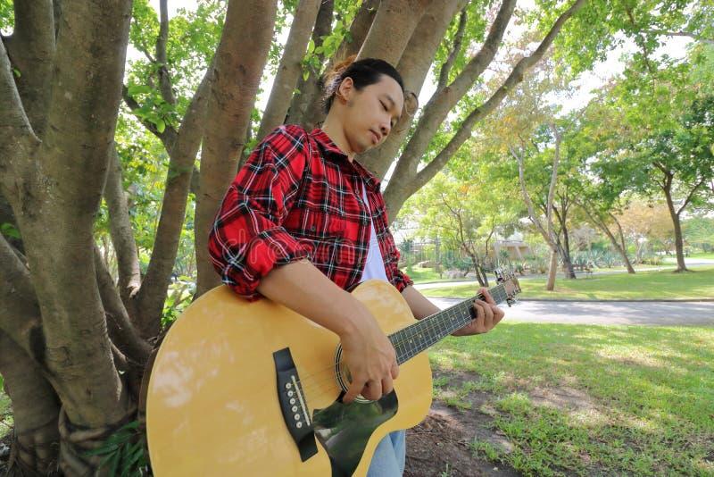 Colpo grandangolare del giovane bello che gioca musica sulla chitarra acustica in un bello fondo della natura fotografie stock libere da diritti