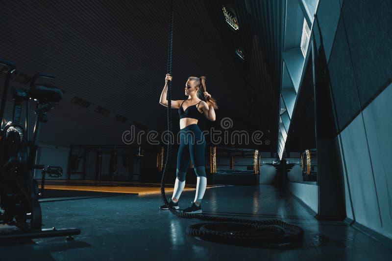 Colpo grandangolare integrale di una donna che esegue le salite della corda alla palestra Fondo di Copyspace immagini stock libere da diritti