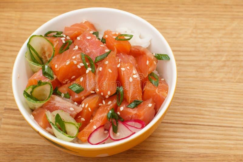 Colpo hawaiano con il salmone e semi di sesamo, riso bollito, cetriolo fresco, ravanello e cipolle verdi in ciotola di vetro immagini stock