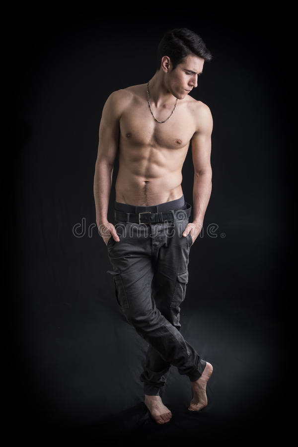 Colpo integrale di bello, giovane senza camicia di misura che porta soltanto i pantaloni immagine stock