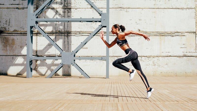Colpo integrale di giovane atleta femminile che sprinta nella città fotografie stock