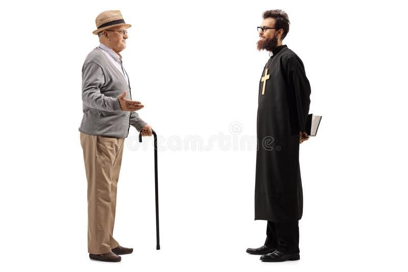 Colpo integrale di un uomo senior con la canna che parla con sacerdote fotografia stock libera da diritti