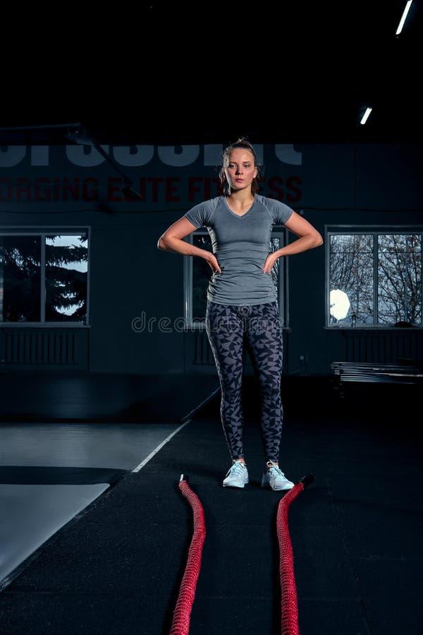 Colpo integrale verticale di una donna atletica di forma fisica che fa esercizio di allenamento funzionale con le corde di battag fotografia stock