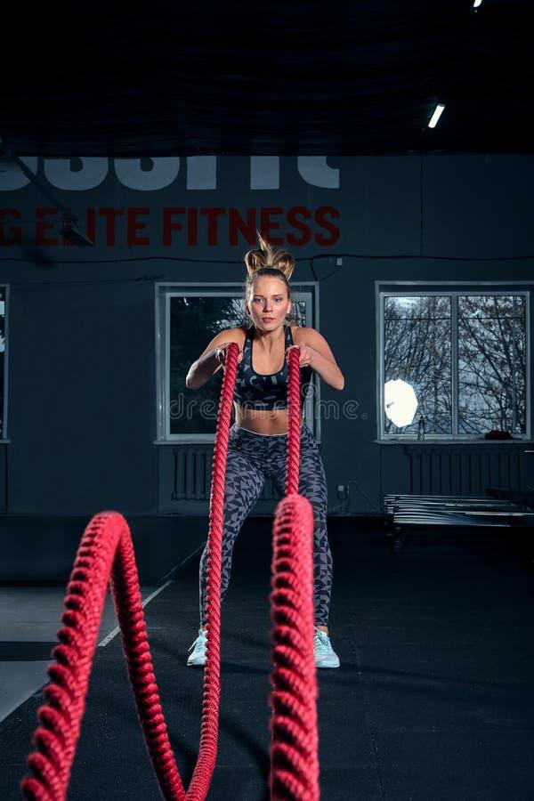 Colpo integrale verticale di una donna atletica di forma fisica che fa esercizio di allenamento funzionale con le corde di battag fotografia stock libera da diritti