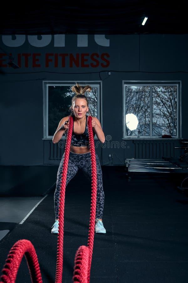 Colpo integrale verticale di una donna atletica di forma fisica che fa esercizio di allenamento funzionale con le corde di battag immagine stock libera da diritti