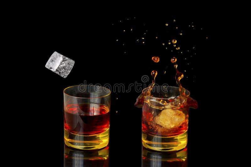 Colpo isolato di whiskey con spruzzata su fondo nero immagine stock
