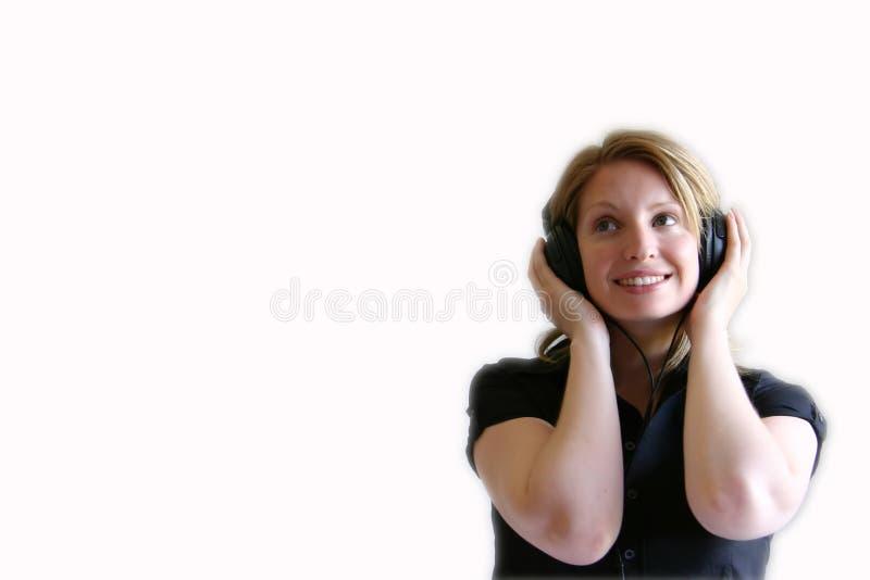 Colpo laterale della ragazza che sorride con le cuffie e la musica fotografia stock