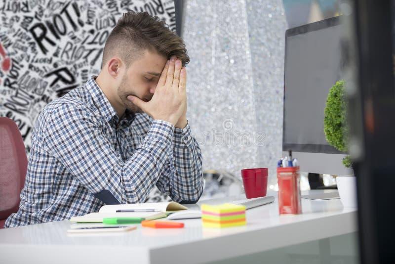 Colpo laterale di profilo di giovane imprenditore frustrato della brunetta, urlante al suo computer portatile in ufficio e crampi immagine stock