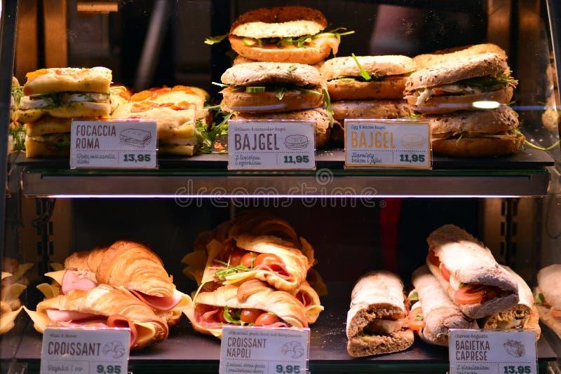 Colpo luminoso degli hamburger, delle guarnizioni di gomma piuma e dei panini in un caffè di Starbucks Vetrina brillante di pasto fotografia stock libera da diritti