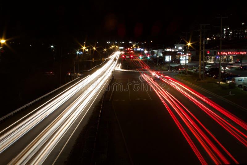 Colpo lungo di esposizione di una strada principale occupata alla notte con le tracce leggere delle automobili sulla strada fotografie stock libere da diritti