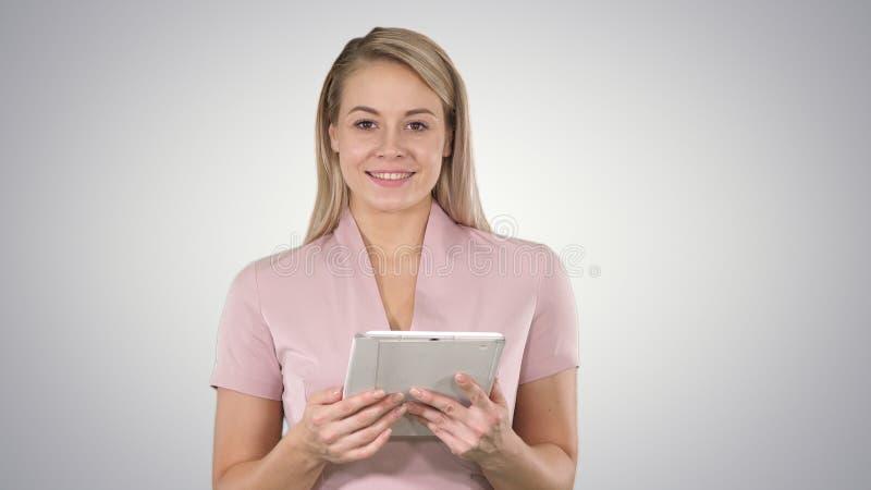 Colpo medio di bella donna che usando le pagine di giro della compressa e guardando nella macchina fotografica sul fondo di pende fotografie stock libere da diritti