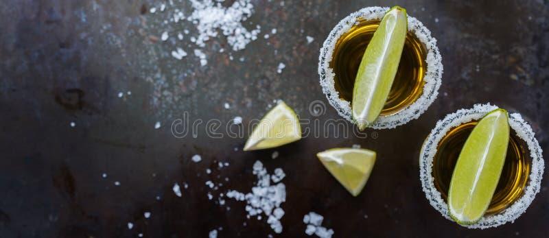 Colpo messicano dorato di tequila con calce e sale verdi immagine stock