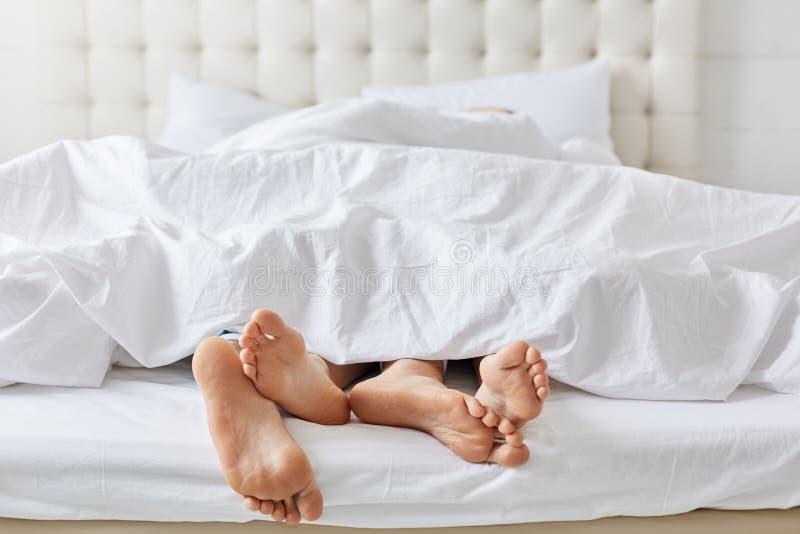 Colpo orizzontale dei piedi delle coppie sotto le coperte da letto bianche a letto alla camera da letto, godendo di buon resto a  fotografie stock libere da diritti