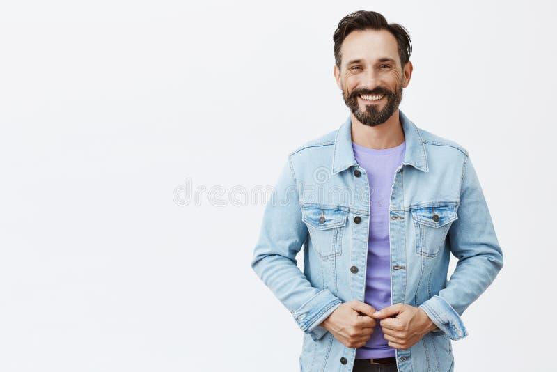 Colpo orizzontale del celibe ottimista e riuscito incantante con la barba e dei baffi in rivestimento del denim, sorridente alleg fotografie stock libere da diritti