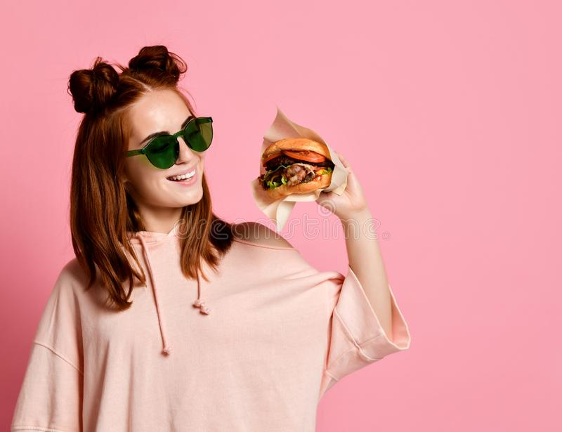 Colpo orizzontale dello studio dell'hamburger grazioso della tenuta della giovane donna immagine stock