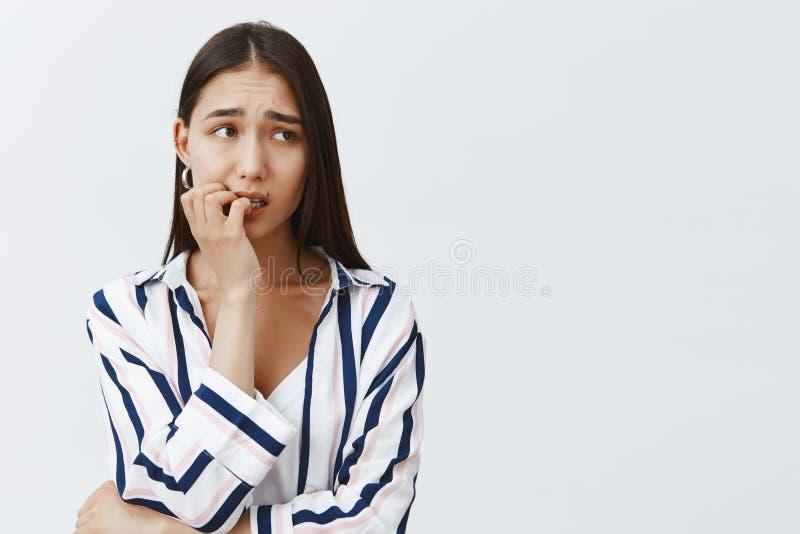 Colpo orizzontale di bella studentessa ansiosa in blusa a strisce, unghia mordente nervoso, aggrottanti le sopracciglia e fotografie stock