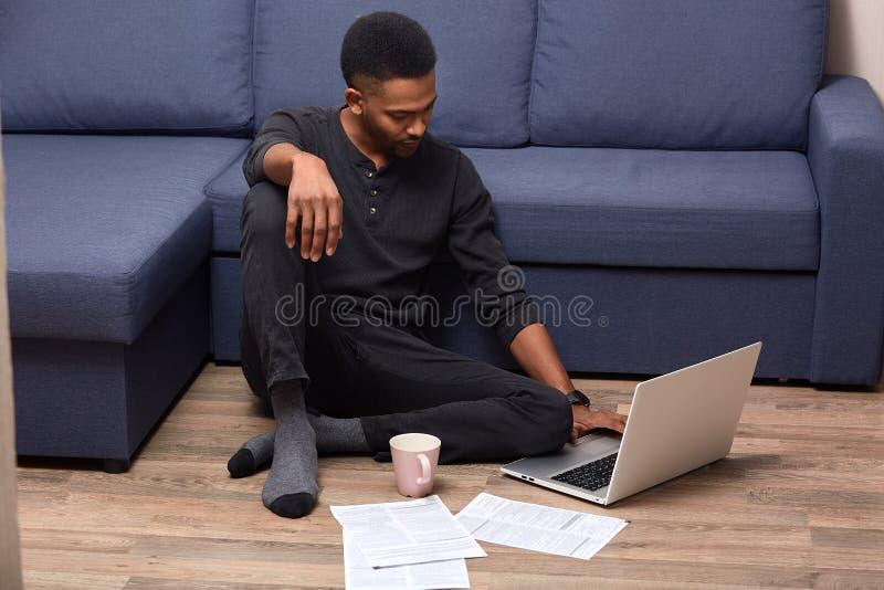 Colpo orizzontale di giovane maschio bello pelato scuro che fa lavoro di ufficio a casa, controllando i documenti, bevanda calda  immagini stock
