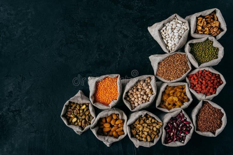Colpo orizzontale di piccoli sacchi riempiti di mandorle, noci, uva passa, cece, fagiolo nano, goji rosso, sopra buio fotografia stock libera da diritti