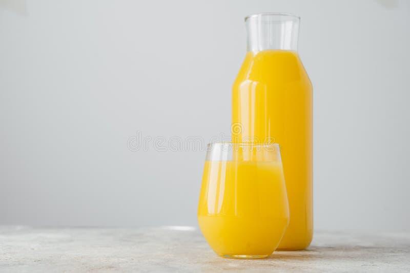 Colpo orizzontale di succo d'arancia di recente schiacciato fatto dell'agrume in contenitori di vetro, isolato sopra fondo bianco immagini stock libere da diritti