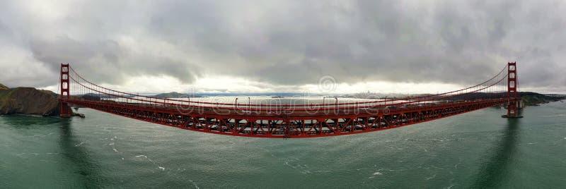 Colpo panoramico dell'pesce-occhio di grande ponte sospeso rosso con le nuvole grige nel cielo fotografia stock