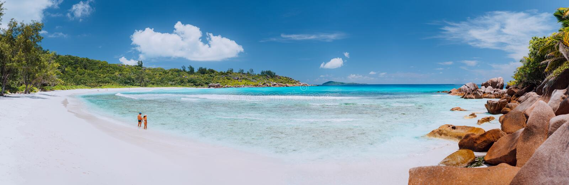 Colpo panoramico di ampia spiaggia di sabbia bianca pittoresca, Seychelles, La Digue, Cocos di Anse Coppia il tempo enyoing di vo immagini stock libere da diritti
