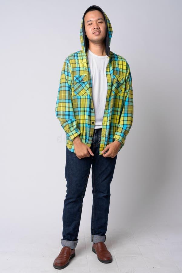 Colpo pieno del corpo della maglia con cappuccio d'uso del giovane uomo asiatico dei pantaloni a vita bassa fotografia stock libera da diritti
