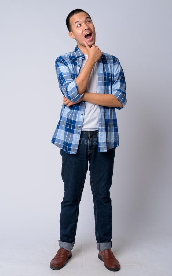 Colpo pieno del corpo di giovane pensiero asiatico felice dell'uomo dei pantaloni a vita bassa fotografia stock libera da diritti