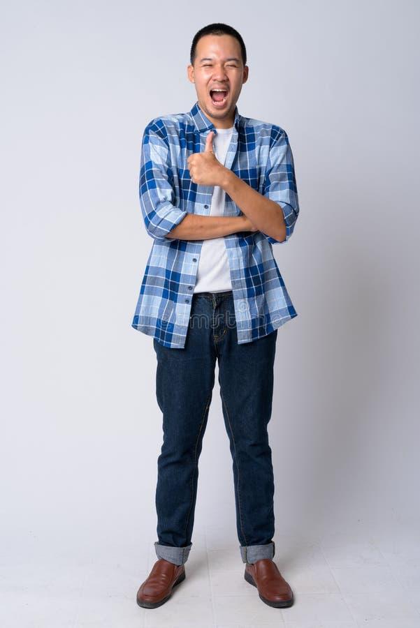 Colpo pieno del corpo di giovane uomo asiatico felice dei pantaloni a vita bassa che dà i pollici su fotografie stock