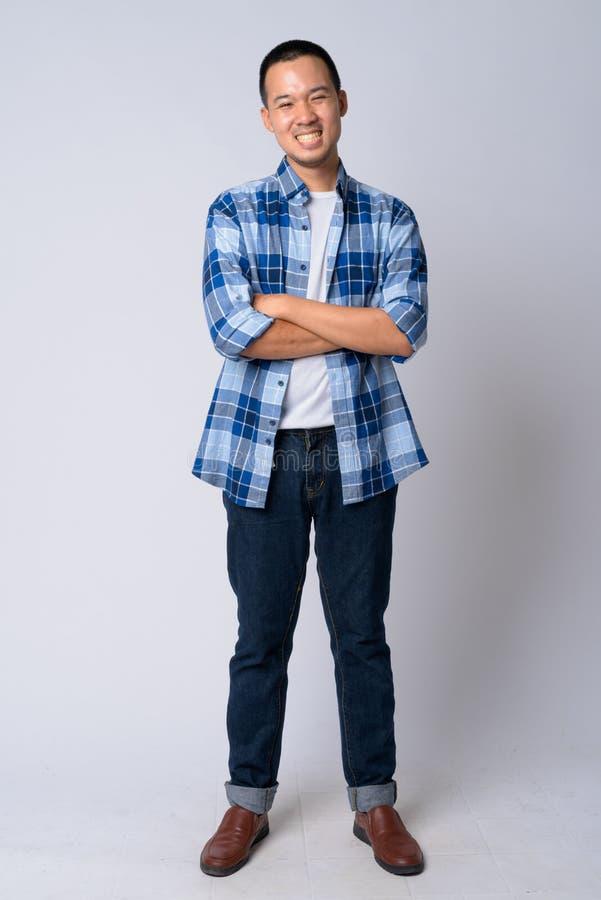 Colpo pieno del corpo di giovane uomo asiatico felice dei pantaloni a vita bassa che sorride con le armi attraversate fotografie stock