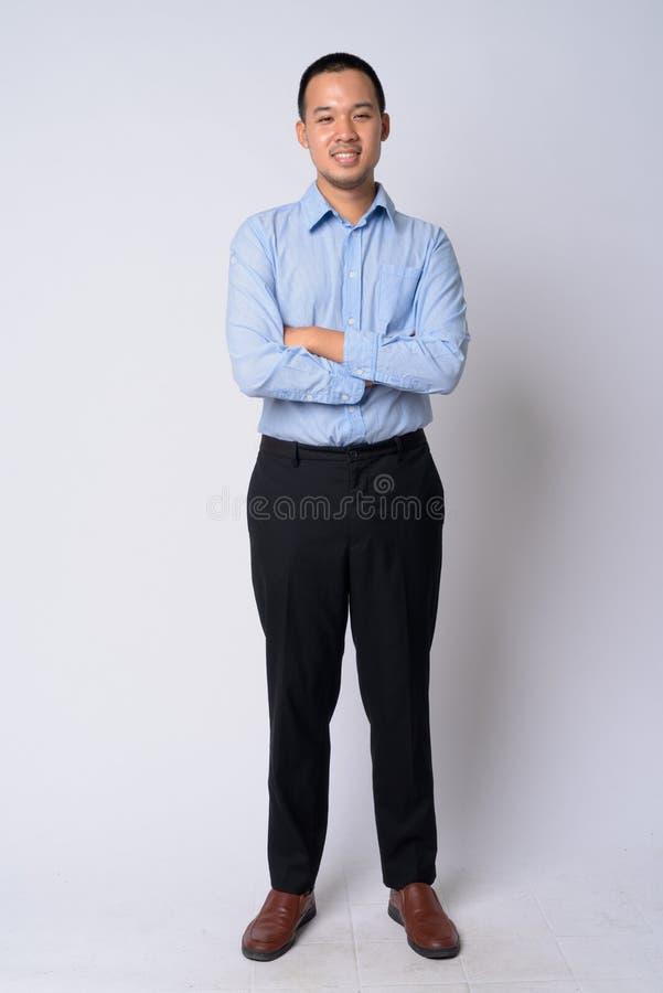 Colpo pieno del corpo di giovane uomo d'affari asiatico felice che sorride con le armi attraversate immagine stock libera da diritti