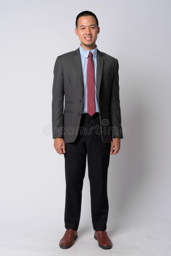 Colpo pieno del corpo di giovane uomo d'affari asiatico felice in vestito immagine stock