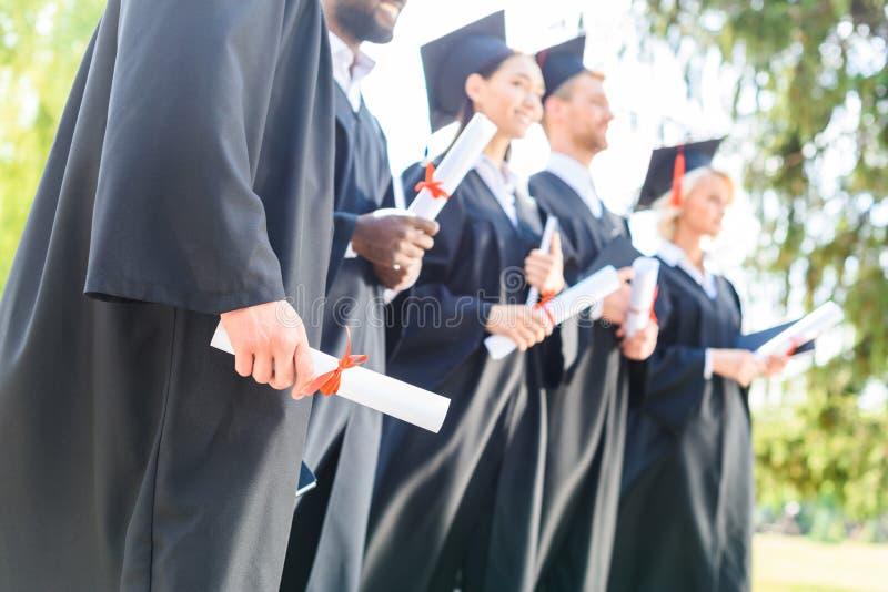 colpo potato degli studenti graduati in capi e nella tenuta dei cappelli fotografia stock