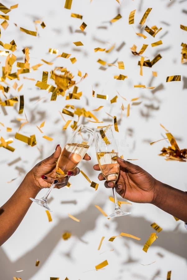 colpo potato dei vetri tintinnanti delle coppie afroamericane di champagne su bianco immagine stock libera da diritti