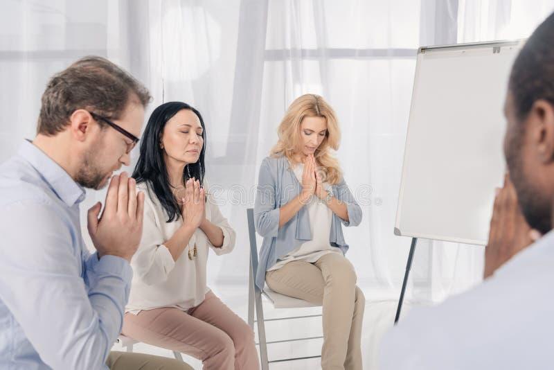 colpo potato del gruppo anonimo di gente multietnica che prega durante immagini stock libere da diritti