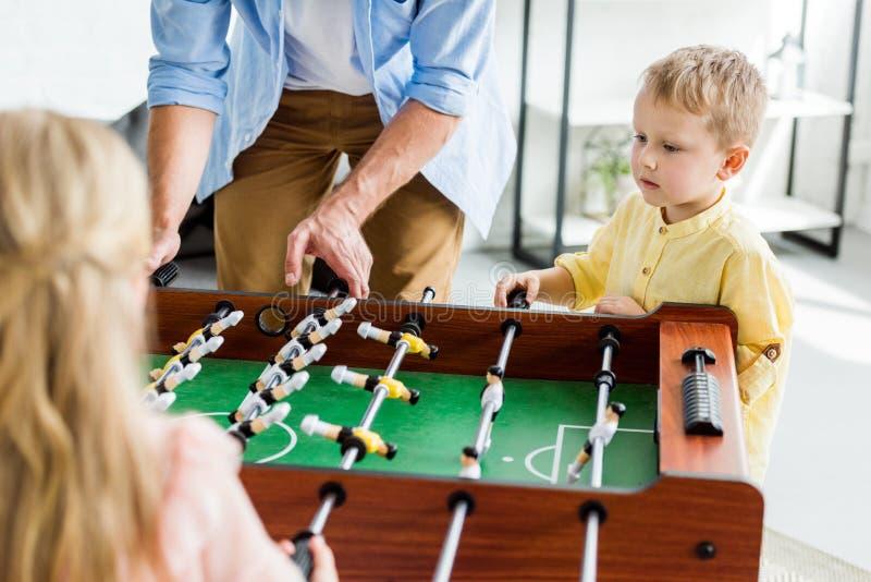 colpo potato del padre con i bambini svegli che giocano calcio-balilla fotografia stock libera da diritti