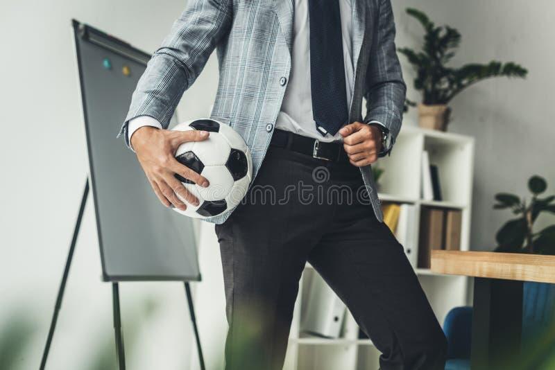 colpo potato dell'uomo d'affari con pallone da calcio immagini stock libere da diritti