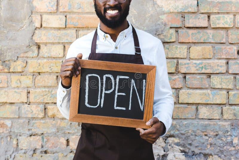 colpo potato della condizione aperta sorridente di attimo del giovane di barista segno afroamericano della tenuta immagine stock libera da diritti