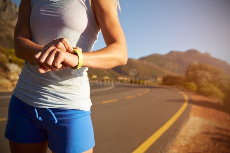 Colpo potato della donna che controlla il suo orologio sportivo fotografie stock libere da diritti