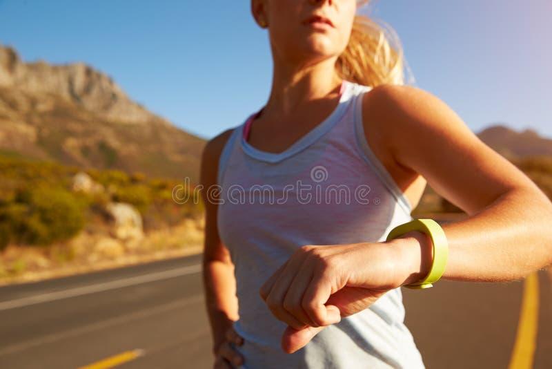 Colpo potato della donna che esegue e che controlla il suo orologio sportivo fotografie stock