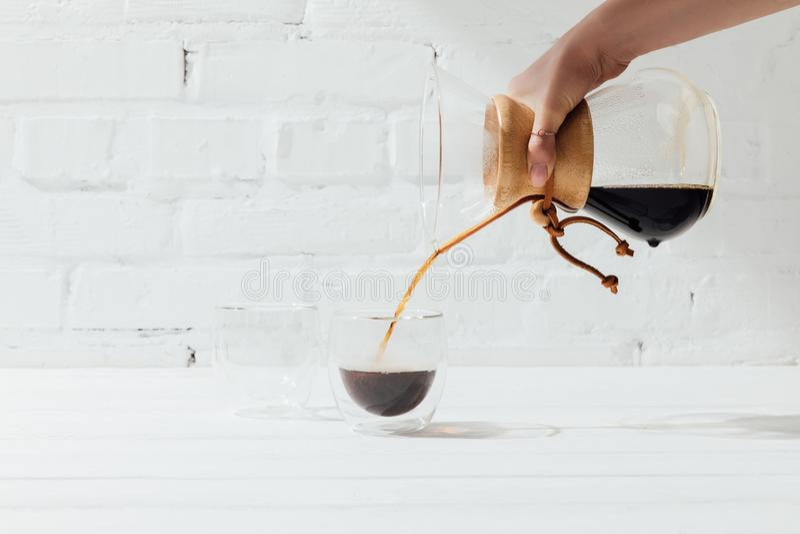 Colpo potato della donna che versa caffè alternativo da chemex nella tazza di vetro fotografie stock