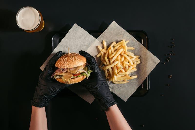 colpo potato della persona in guanti che tengono hamburger saporito sopra il vassoio con le patate fritte ed il vetro di birra su fotografie stock libere da diritti