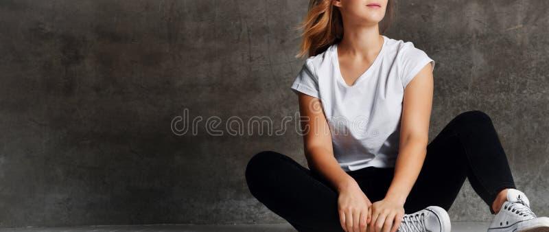 Colpo potato della ragazza in jeans che si siedono sul pavimento vicino alla parete grigia fotografie stock libere da diritti