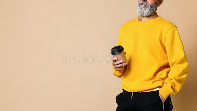 Colpo potato di un anziano allegro che tiene una tazza di caffè macchiato e che esamina la macchina fotografica immagine stock