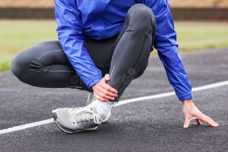Colpo potato di un giovane che tiene la sua caviglia nella distorsione di dolore una f immagini stock libere da diritti